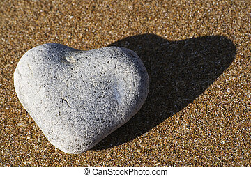 Heart shaped stone on a sandy beach - A heart shaped stone...