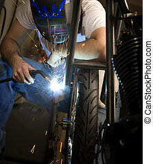 Welder working on motorcycle - Welder working on the metal...