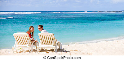 Honeymooners -  Young happy couple on white sand beach