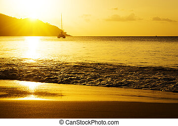 Yacht near rocky coast of seychelles Gold sunset on sand...