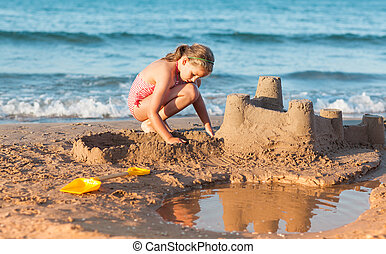 Child builds sandcastle on the beach - Relaxed child builds...