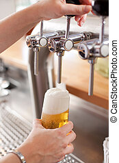 Bartender pouring draft beer - Bartender pouring a pint of...