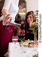 Serving red wine in a restaurant - Waitress serving red wine...