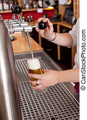 Dispensing fresh draft beer - View behind the counter in a...
