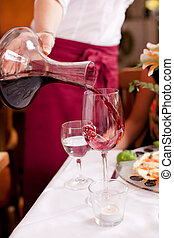 Waitress pouring red wine from a decanter into an elegant...