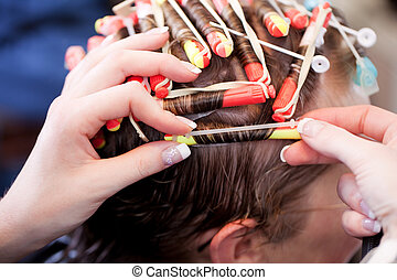 Hairstylist doing a perm - Closeup of the hands of a female...