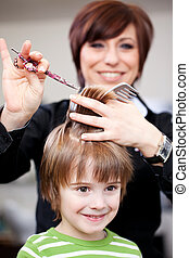 Cute little child getting a haircut from a smiling female...