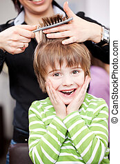 Cute young child at the hairdresser laughing with his hands...