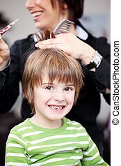 Young child in a hairdressing salon having a hair cut from a...