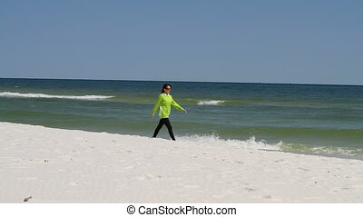 Woman Walking Beach - Woman walks along a sandy beach...
