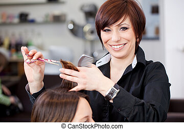 Friendly hairstylist cutting hair - Friendly attractive...