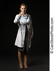 Full length portrait of doctor woman threatening with finger isolated on black