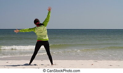 Woman Stretching Beach - Thin athletic woman performs...
