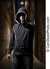 Thief on a dark alley - Thief in the hood pointing a gun, on...