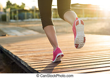 Outdoor runner - Young woman is running in sunny nature