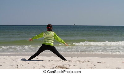 Woman Beach Stretching - Fit woman limbers up on a sandy...