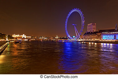 The London eye and the River Thames by night, London, UK -...
