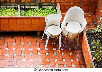 Stacks of Chairs on Patio in Rain - Stacks of platic chairs...