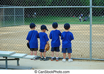 Looking out at the field - four little boys look out onto a...