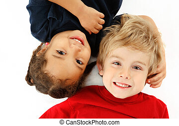 Best friends - two young childen lay head to head on the...