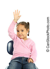 Little girl raising her hand - a young girl sits in a school...