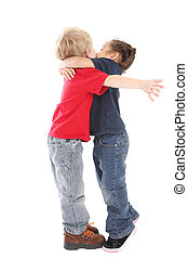 a surprise kiss and hug - two young children enthusically...