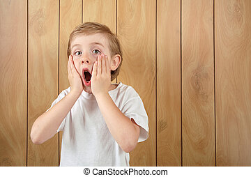 Surprised boy - a young boy holds his face with an...