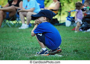 tired at first base - a young boy takes a break while on...