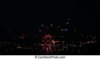 Fireworks flashing in the nightsky above the city.
