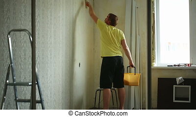 Renovation. - Young man spreading glue over the wall before...