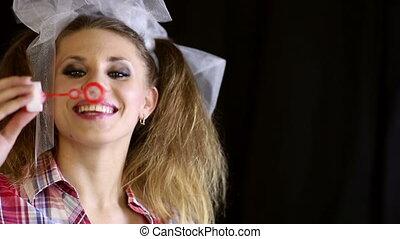 Soap bubbles - Young woman blowing soap bubbles.
