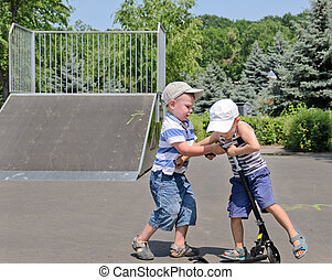 Two young boys fighting over a scooter - Two young boys in...
