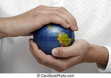 Businessman holding globe - Businessman holding and examing...
