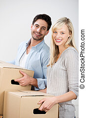 Couple Carrying Cardboard Boxes At Home - Portrait of happy...