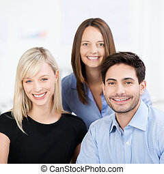 Smiling business team with a man and his two female...