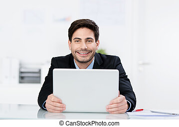 Happy Businessman Holding Laptop At Desk