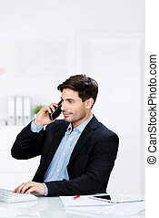 Businessman talking on the telephone in his office listening...