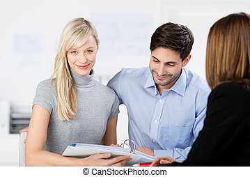 Couple looking at paperwork in a meeting - Attractive...
