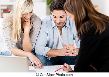 Financial Advisor Explaining Document To Couple At Table -...