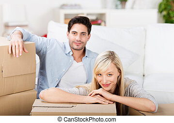 Couple With Cardboard Boxes At Home - Portrait of mid adult...