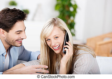 Woman Conversing On Cordless Phone While Man Looking At Her...