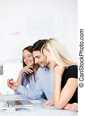 Motivated business team working on a laptop