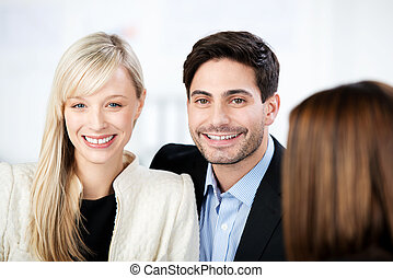 Couple Smiling With Financial Advisor In Foreground -...