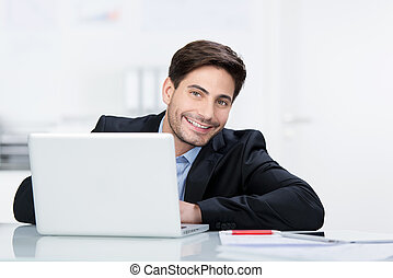 Smiling businessman working in front of his laptop