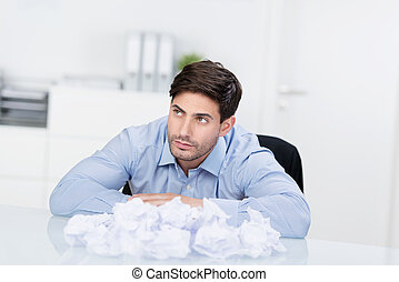Young handsome businessman sitting at desk with crumpled...