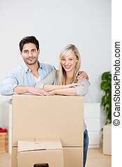 Smiling young couple moving house standing close together...