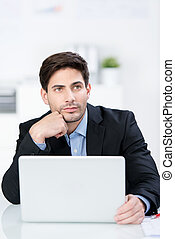 Businessman With Laptop Looking Away At Desk - Thoughtful...