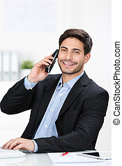 Businessman Using Cordless Phone At Desk - Portrait of happy...