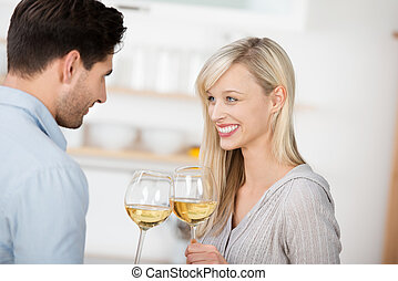Couple Toasting Wine Glasses In Kitchen - Happy mid adult...