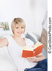 Woman reading a book on a couch - Beautiful young woman...